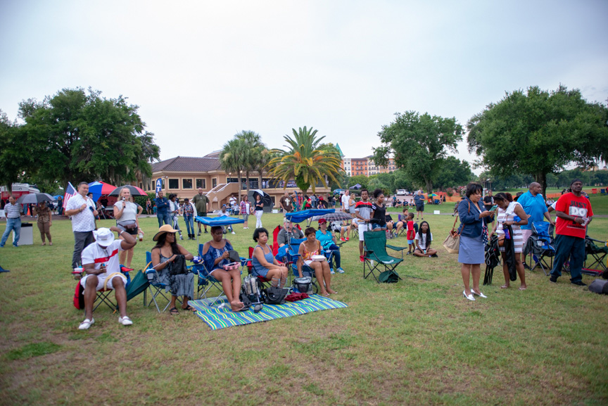 Crowd sitting in lawn chairs, listening to music