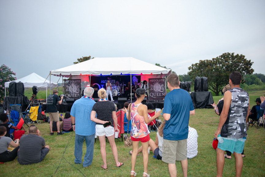 Crowd standing in front of music stage, listening to music