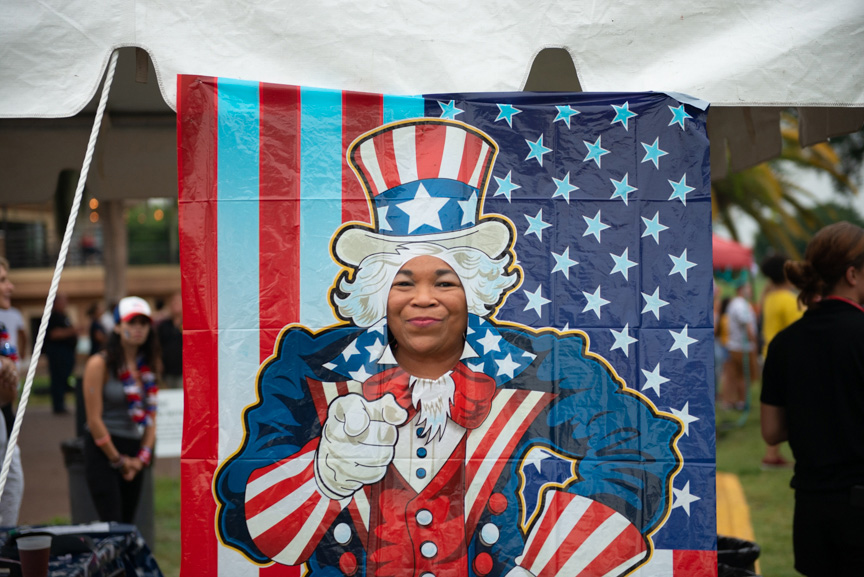 Smiling woman getting her picture taken with Uncle Sam photo booth