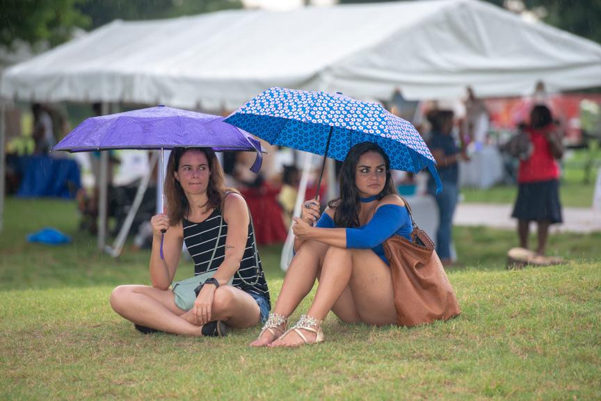 Women sitting under umbrellas in the rain during Music Works festival
