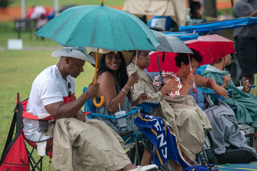 Festival goers listening to music under umbrellas in the rain