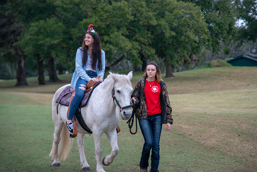 Young woman riding white horse