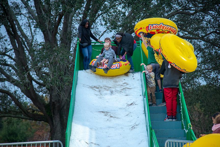 Families sledding down snow slide at winter fest