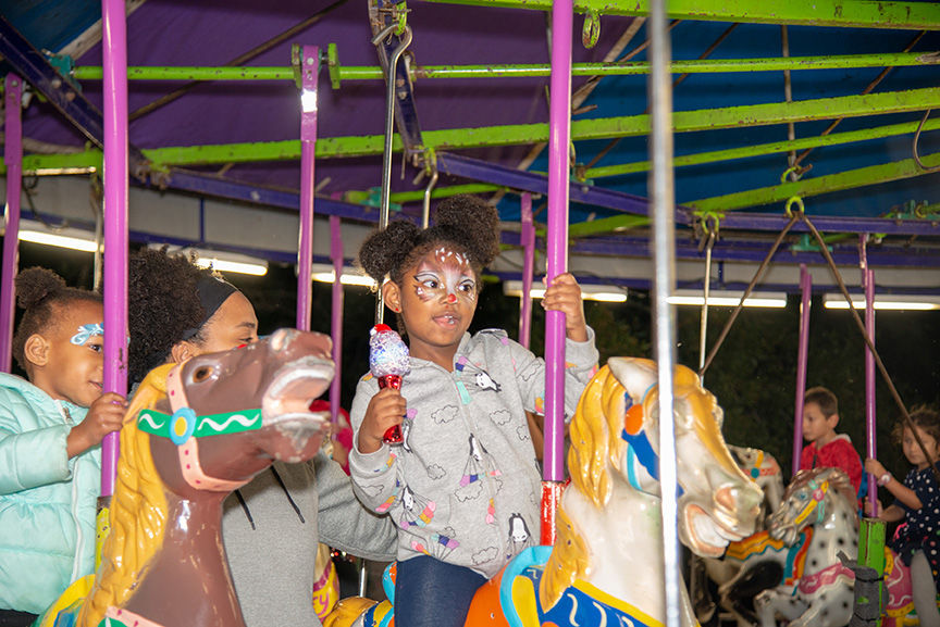 Little girl in facepaint, riding a carousel