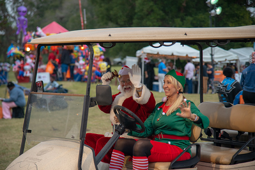 Santa and elf riding in gold cart